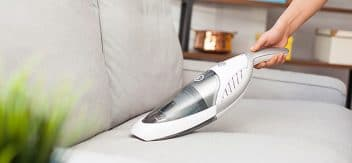Cleaning sofa with portable vacuum cleaner