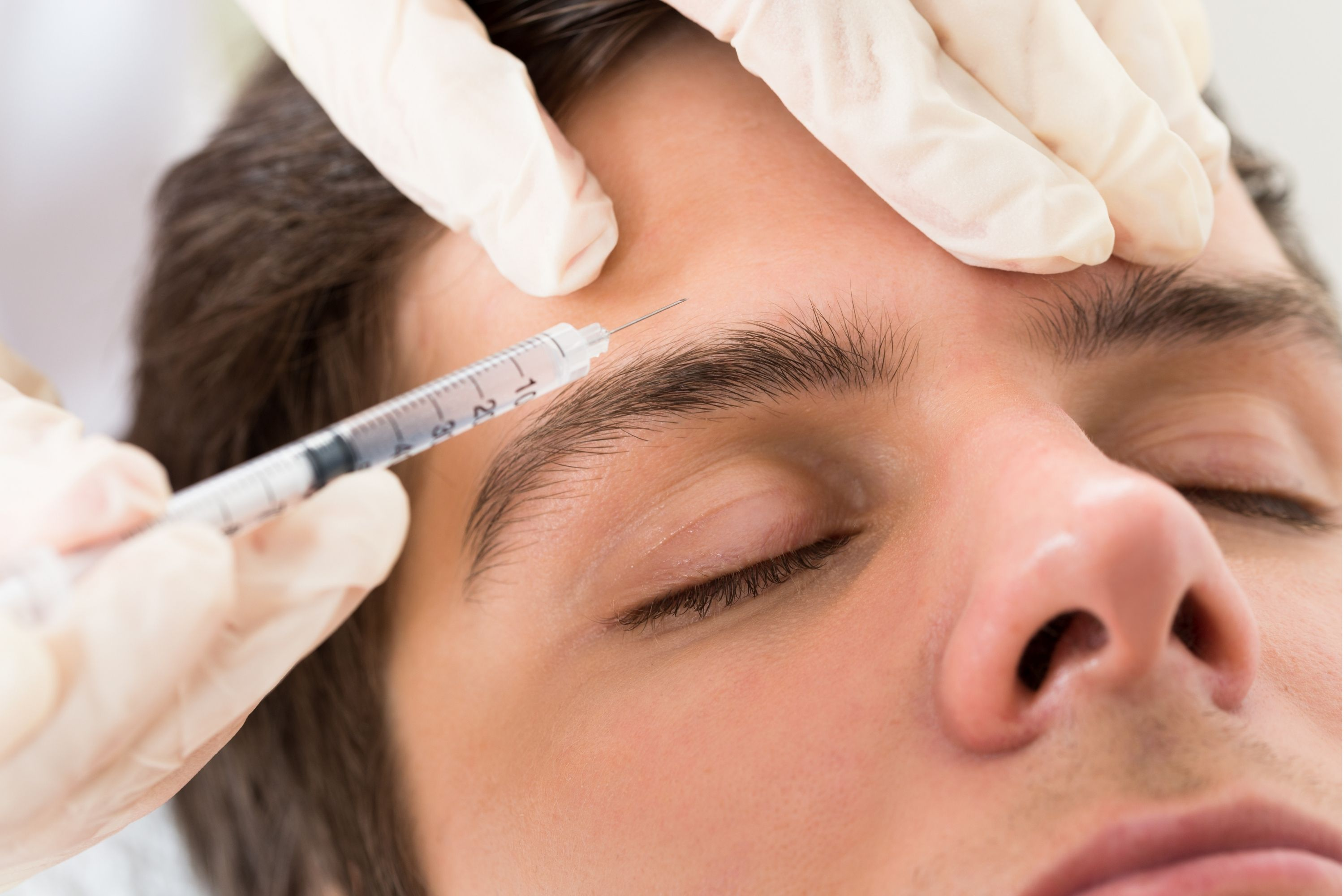 A man receiving Botox injections on the forehead